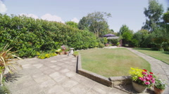 Exterior view of  a traditional British home and well kept garden on a sunny day Stock Footage