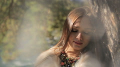 Stock video footage beautiful girl in the forest in the sun hugging a huge tr - stock footage