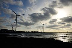 eletric power generator wind turbine over a cloudy sky in jeju coast - stock photo