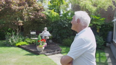 Cheerful senior couple relaxing in the garden at home - stock footage