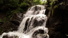 Waterfall flows rapidly through the stone cliffs Stock Footage
