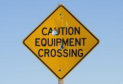 Caution equipment crossing sign Stock Photos