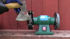 Sharpening axe tool on electrical grinder stone Stock Footage
