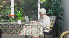 Cheerful senior lady relaxing in the conservatory with laptop computer - stock footage