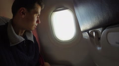 Bored airplane passenger looking into porthole, aircraft boredom - stock footage