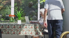 Cheerful senior couple relaxing in the conservatory with laptop computer - stock footage