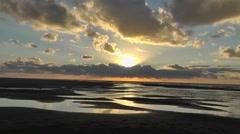 Sun setting behind a cloud over a sandy beach Stock Footage