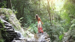Young woman rises hands at waterfall in jungle Koh Samui. Thailand. HD. Stock Footage