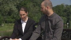 Shy students in park having friendly conversation, beautiful man woman on bench Stock Footage