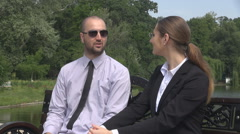 Stock Video Footage of Business couple outdoors talking, man woman in park sitting on bench clock check