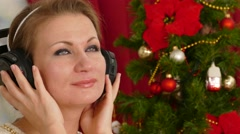 Beautiful adult woman listening music against Christmas tree - stock footage