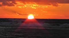 Orange sunset over the sea, birds flying past in the background Stock Footage