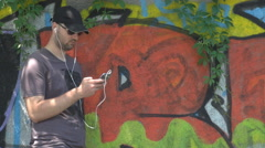 Graffiti wall background, young boy with set earphones on, listening music  Stock Footage