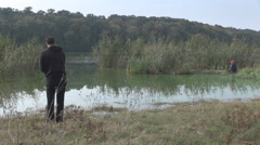 Summer day windless, nice water reflection in lake, young man with rod fishing  Stock Footage