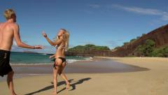 Attractive young couple frolick on Big Beach, Maui on sunny day Stock Footage