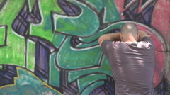 Man with face on graffiti wall being upset, single boy helpless, difficult life Stock Footage