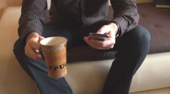 Morning cup of coffee in living room businessman with smartphone relaxation time Stock Footage