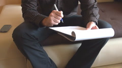 Man headless view working with clipboard papers, writing and studying for work - stock footage