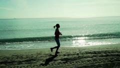 Silhouette of young woman jogging along the beach, super slow motion 120 fps  HD Stock Footage