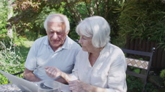 Cheerful senior couple relaxing in the garden with computer and glass of wine - stock footage