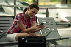 Young, pretty woman with smartphone sitting in the train station NTSC Stock Footage