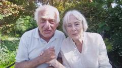 Cheerful senior couple having a skype conversation in the garden - stock footage