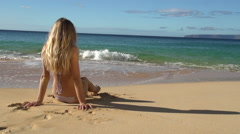 Swim suit mode sits on a beach in Maui Stock Footage