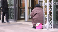 Poor beggar old woman  at the entrance to a large shopping center Stock Footage