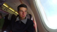 Male Caucasian man airplane passenger looks porthole, air flight, click for HD Stock Footage