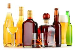 bottles and glasses of assorted alcoholic beverages isolated on white backgro - stock photo