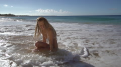 bikini model in a candid shot on the waters edge on a beach in Maui - stock footage