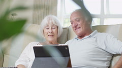 Cheerful senior couple relaxing at home with a computer tablet - stock footage