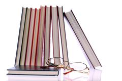 Hardcover books and glasses on white background Stock Photos