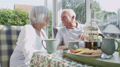 Affectionate senior couple drinking coffee in conservatory on a sunny day - stock footage