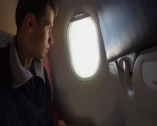 Bored airplane passenger looking into porthole, aircraft boredom, click for HD - stock footage