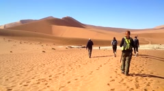 People hike towards the highest dunes in the world in Namibia, Africa. Stock Footage