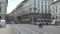 Milan downtown traffic street old tram yellow train pass cloudy day pedestrian  Stock Footage