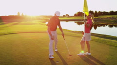 Stock Video Footage of Golf Male Female Caucasian Playing Clubs Green Corporate Sponsor Wealth Leisure