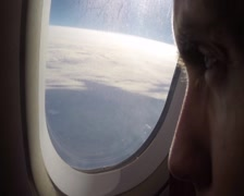 Male eyes closeup airplane flight above ground kilometers height, click for HD - stock footage