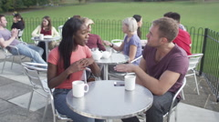 Happy attractive young couple, chatting and laughing together at outdoor cafe - stock footage