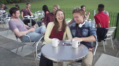 Happy attractive young couple, posing to take their own picture at outdoor cafe - stock footage