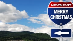 Merry christmas road sign with flowing clouds Stock Footage