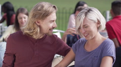 Cute young couple dating, pose to take their own picture at outdoor cafe - stock footage