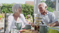Affectionate senior couple drinking coffee in conservatory on a sunny day Stock Footage