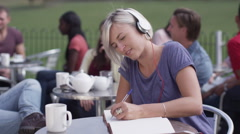 Attractive young woman studying and listening to music at outdoor cafe Stock Footage