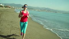 Young attractive female jogger running on the city beach  HD - stock footage