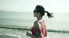 Stock Video Footage of Young pretty female jogger running on the city beach slow motion HD
