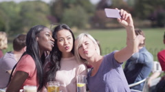 Happy young female friends pose to take their own photo at outdoor cafe Stock Footage