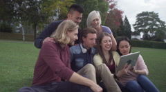 Happy group of friends outdoors in natural setting with computer tablet Stock Footage