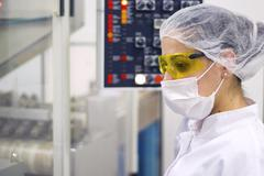 Woman Operating the Control Panel - Pharmaceutical Manufacturing - stock photo